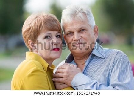 Senior citizen blue shirt and an elderly wife in a yellow dress outdoors. Beautiful married couple of seniors.