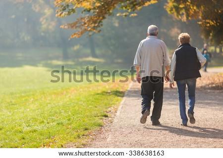 Senior citizen couple taking a walk in a park during autumn morning.  stock photo