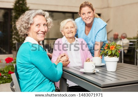 Senior citizen drinks coffee with visit and caregiver on terrace in retirement home