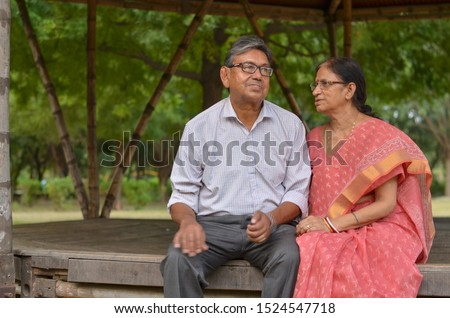Senior citizen Indian couple smiling and laughing in the evening sitting closely in a park in summer in New Delhi, India. Concept love