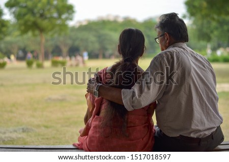 Senior citizen Indian man reads from mobile and with his hand over his wife's shoulder shot from behind on his wife while sitting in a park in Delhi, India. Concept love