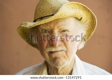Senior Citizen Man Frowning n a Straw Cowboy Hat Foto stock ©