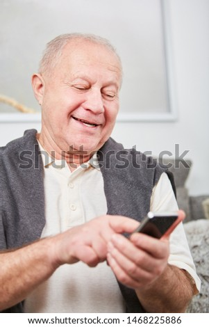 Senior citizen writing a message or SMS with his smartphone
