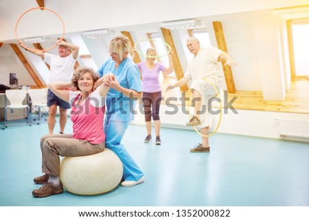 Senior citizens do back training as a course in a nursing home with a physiotherapist
