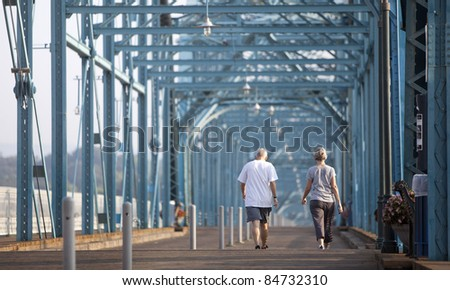 senior citizens walking over bridge