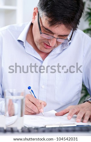 Senior concentrated   business man writing in office