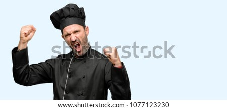 Senior cook man, wearing chef hat happy and excited celebrating victory expressing big success, power, energy and positive emotions. Celebrates new job joyful isolated over blue background