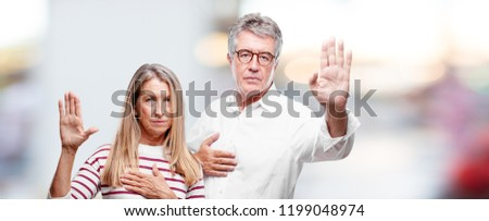 senior cool husband and wife smiling confidently while making a sincere promise or oath, solemnly swearing with one hand over heart.