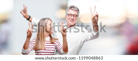 senior cool husband and wife with a proud, happy and confident expression; smiling and showing off success while gesturing victory with both hands, giving an