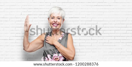 senior cool woman smiling confidently while making a sincere promise or oath, solemnly swearing with one hand over heart.