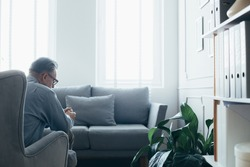 Senior counselor sitting in grey wing back chair in elegant Scandinavian interior waiting for a patient