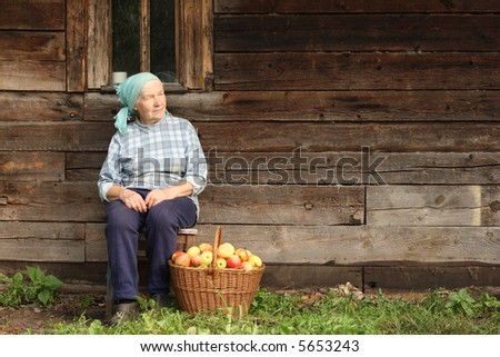 Senior countrywoman sitting against wooden wall with basketful of apples at her feet