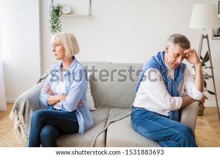 Senior couple after argument sitting on opposite sides of sofa, having relationship problems