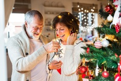Senior couple at home decorating Christmas tree.