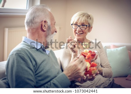 Senior couple at home eating healthy meal.