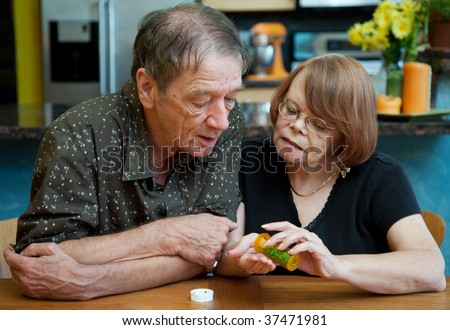 Senior Couple at Home in Kitchen Discussing Medication