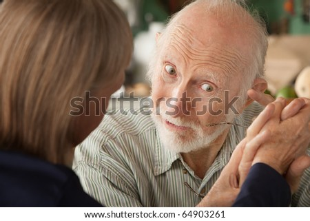 Senior couple at home in kitchen holding hands focusing on man