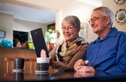Senior Couple At Home Making Video Call To Family Or Watching Movie On Digital Tablet