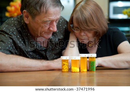 Senior Couple at Home Reading Prescription Bottle Labels