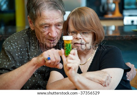 Senior couple at home with prescription bottle