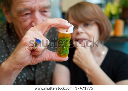 Senior couple at home with prescription bottle, focus