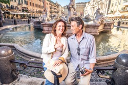 Senior couple at Navona square, Rome - Happy tourists visiting italian famous landmarks