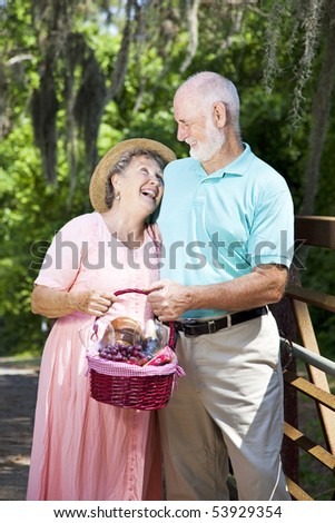 Senior couple carrying a picnic basket and laughing together.