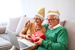 Senior couple celebrating christmas at home and having video conference and keeping a distance, during COVID-19. Seniors in Christmas video call, Online talking with family
