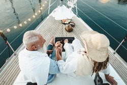 Senior couple celebrating wedding anniversary on sailboat - Happy mature people having fun on boat trip vacation - Love relationship and travel elderly people lifestyle concept