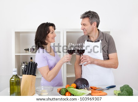 Senior couple cooking at home and drinking wine. Isolated on white