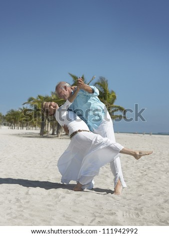 Senior couple dancing at beach on sunny a day