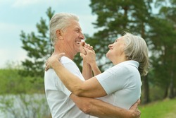 Senior couple dancing near lake