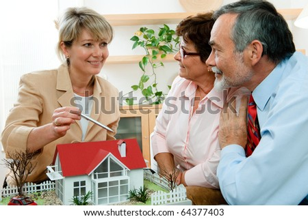 senior couple discussing  with consultant, real estate agent or architect