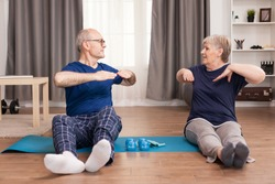 Senior couple doing back exercises sitting on yoga mat. Old person healthy lifestyle exercise at home, workout and training, sport activity at home.