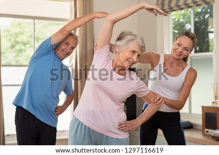 Senior couple doing exercise at home with physiotherapist. Mature gym trainer helping elderly man and old woman exercising at home. Retired husband and wife doing stretching exercises at gym.
