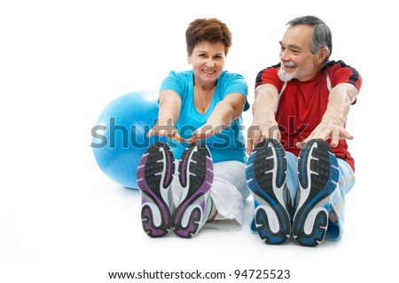 senior couple doing stretching exercise at the gym