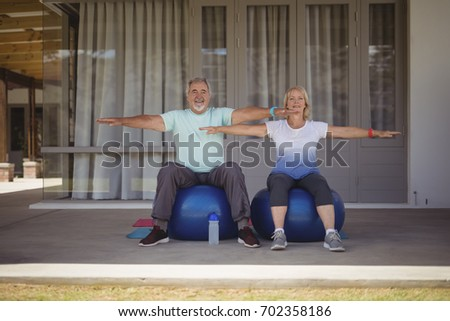Senior couple doing stretching exercise on exercise ball at veranda #702358186