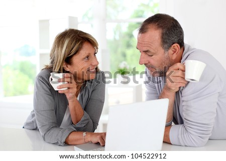 Senior couple drinking coffee in front of laptop computer