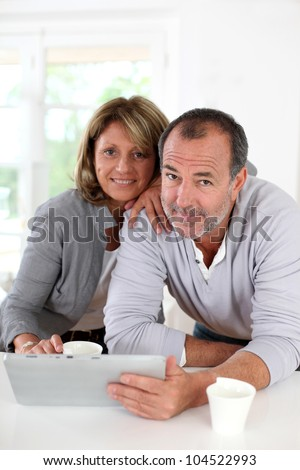 Senior couple drinking coffee in front of tablet