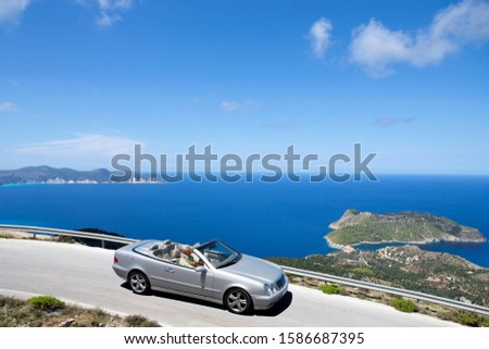 Senior couple driving convertible car along coastal road