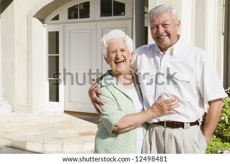 Senior couple embracing outside house