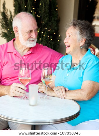 Senior couple enjoying a glass of wine and conversation at an outdoor cafe.