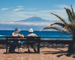 Senior couple enjoying blu skies sea/ocean and mountain view  from island keyside bench in surroundings of a palm. Tourists taking break catching calmness of the sea and restoring the energy.