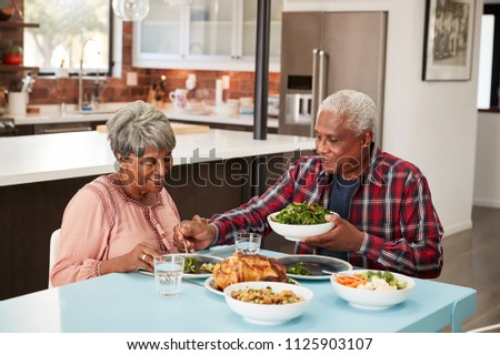Senior Couple Enjoying Meal Around Table At Home #1125903107