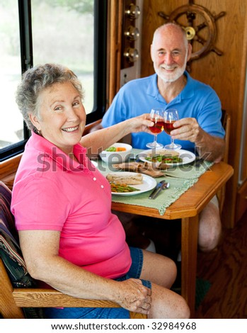 Senior couple enjoys a romantic meal in the kitchen of their motor home.