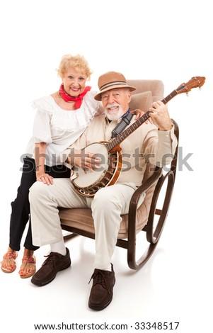 Senior couple enjoys singing and playing country music.  Isolated on white.