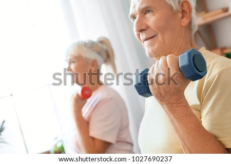 Senior couple exercise together at home health care with dumbbells close-up #1027690237