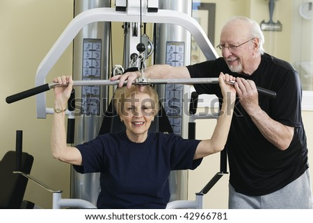 Senior couple exercising in the gym. Horizontally framed shot.
