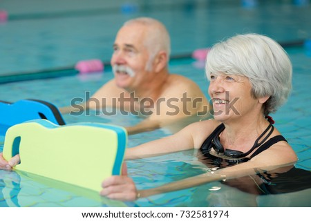 senior couple exercising with floats in swimming pool #732581974