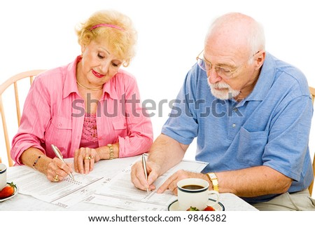 Senior couple filling out absentee ballots at home.  Isolated on white.